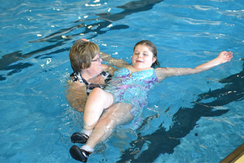A student floats on her back in a pool while being held up by the swimming instructor.