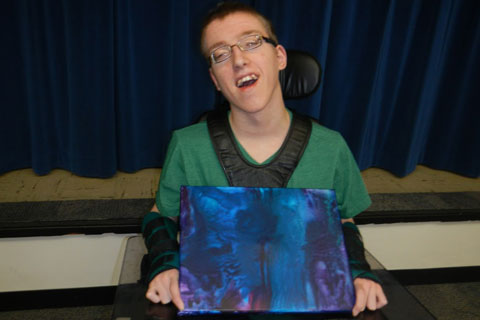 A student proudly displays a painting he created.