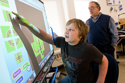 A student points to an opject on a smartboard while his teacher looks on.
