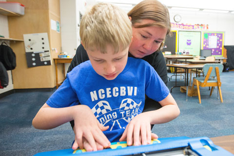 A teacher helps a students learn how to use a braille keyboard.