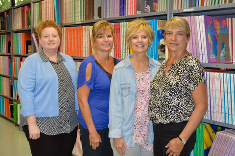Three Nebraska Instructional Resource Center staff members smiling in front of book shelves in the library.